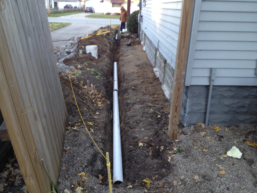 After digging out about 4 feet and down 28 inches, I through the dirt back up against the foundation so the dirt was graded towards the deep part of my trench. I placed pipe in to make sure it was deep enough and pitched towards my drainage spot.